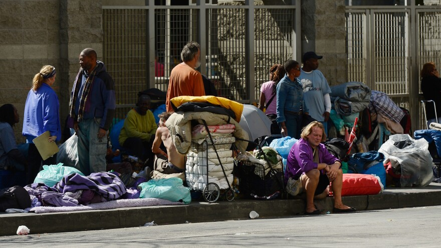 """Homeless people rest on a public sidewalk early this year in downtown skid row area of Los Angeles. The United Way of Greater Los Angeles is attempting to end """"chronic homelessness"""" by 2016 with a model that identifies the neediest cases and provides them with permanent homes."""