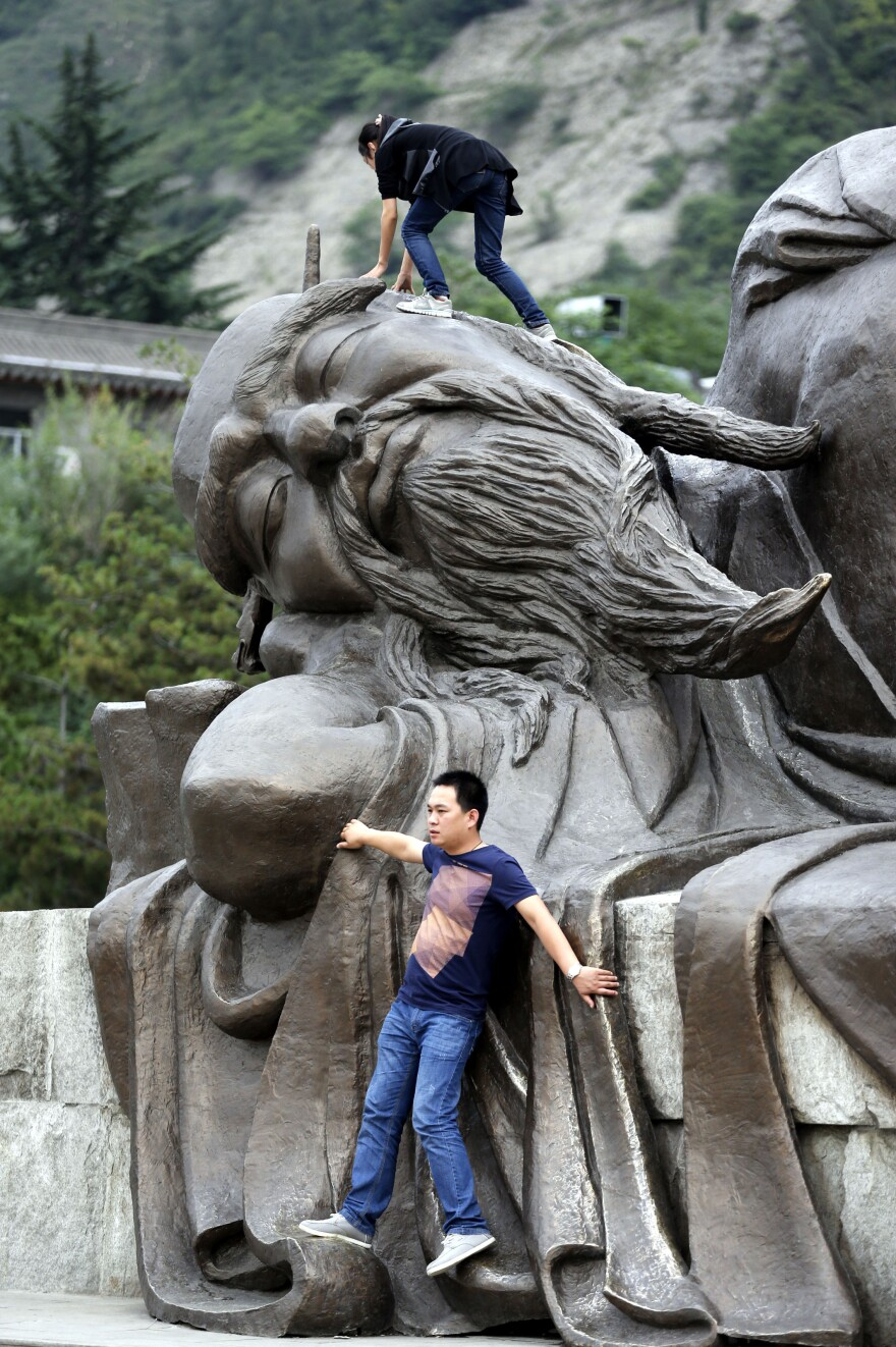"""Not exactly what that's for: Two tourists climb on a statue in Huayin, China, near <a href=""""http://www.npr.org/blogs/thesalt/2015/04/21/401253598/tea-tao-and-tourists-china-s-mt-hua-is-three-part-harmony"""">Huashan,</a> or Mount Hua, a famed tourist destination, in May 2013."""