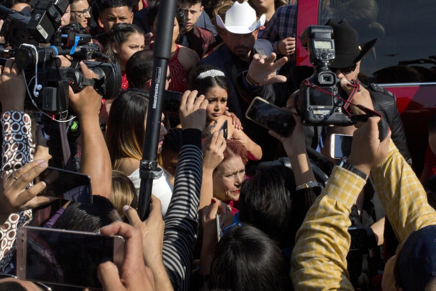 Journalists surround Rubi Ibarra as she arrives at the site of a Mass during her 15th birthday party. Her daylong celebration was reportedly attended by thousands, and for some portions tens of thousands, of people.