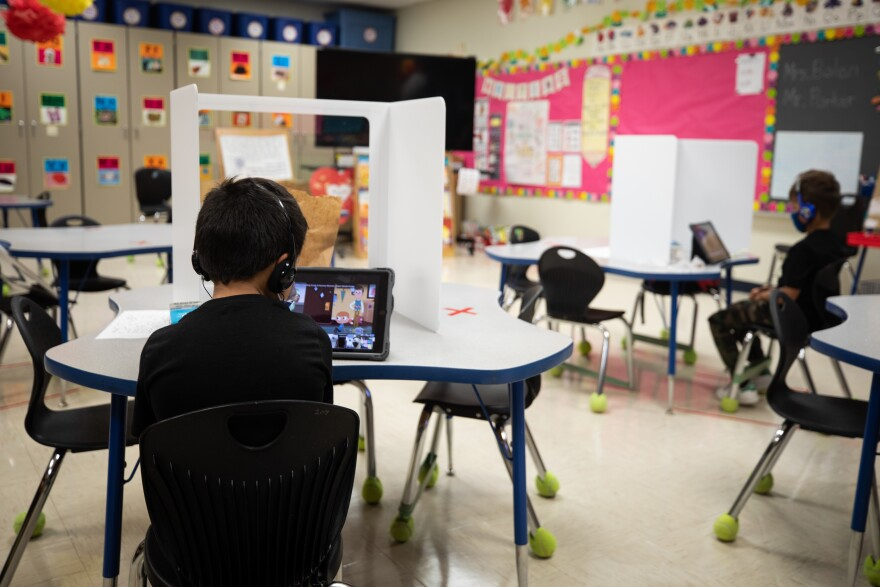 A student learns on his tablet during a class at Boone Elementary School in South Austin. He is one of a few children in a classroom, while many classmates participate via Zoom from home.