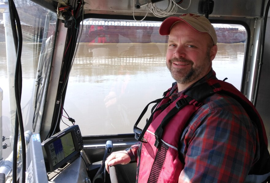 """SIUC faculty member Jonathan Remo, who was part of Monday's """"St. Louis on the Air"""" discussion of water policy, passes a barge while captaining a research vessel near Grand Tower, Illinois."""