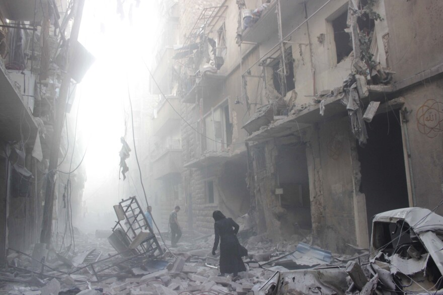 A Syrian woman makes her way through debris following an airstrike by government forces in the northern city of Aleppo on Tuesday. Government forces have the momentum and are pushing to drive the rebels out of Syria's largest city.