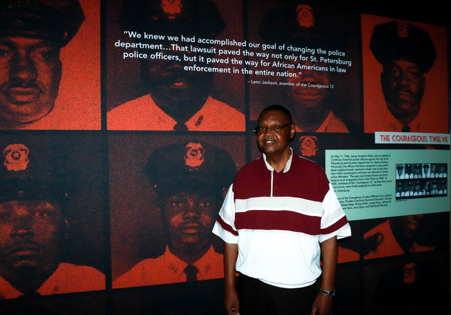 Leon Jackson stands next to a photo of himself from his time as an officer during the civil rights era.