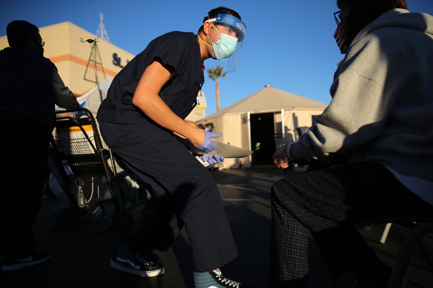A California National Guard medic prepares to check the vital signs of an incoming patient before triage tents outside St. Mary Medical Center last week in Apple Valley amid a surge in COVID-19 patients in Southern California.