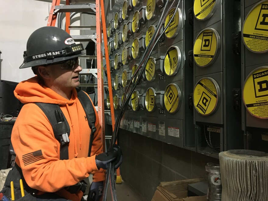 A man in an orange sweatshirt and grey helmet works on an electrical panel.