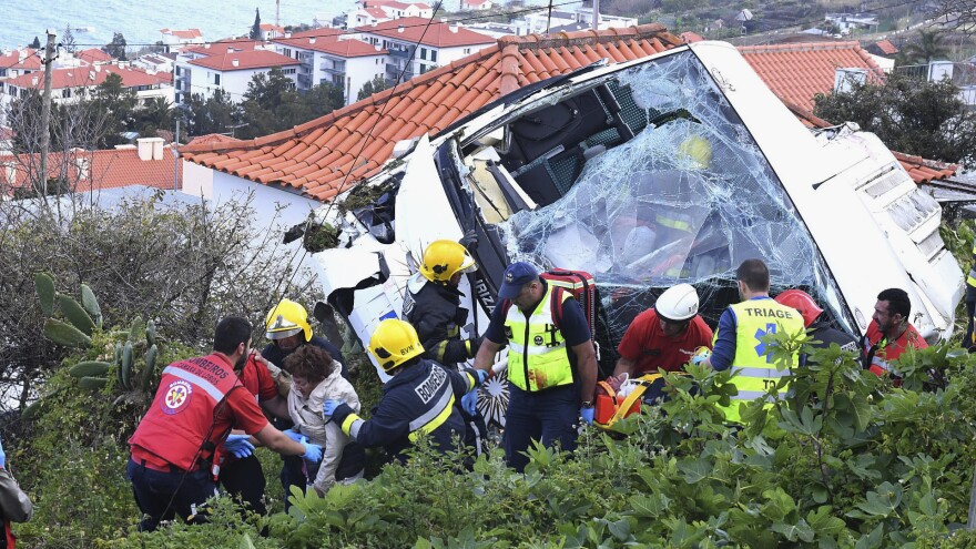 Rescue workers help a person who was inside a tour bus that crashed Wednesday in Caniço, a coastal town on Portugal's island of Madeira.