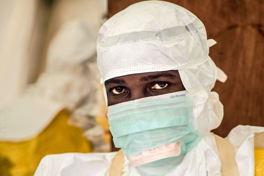 A health worker just needs goggles to complete the protective suit for the Ebola treatment center in Kailahun, Sierra Leone.