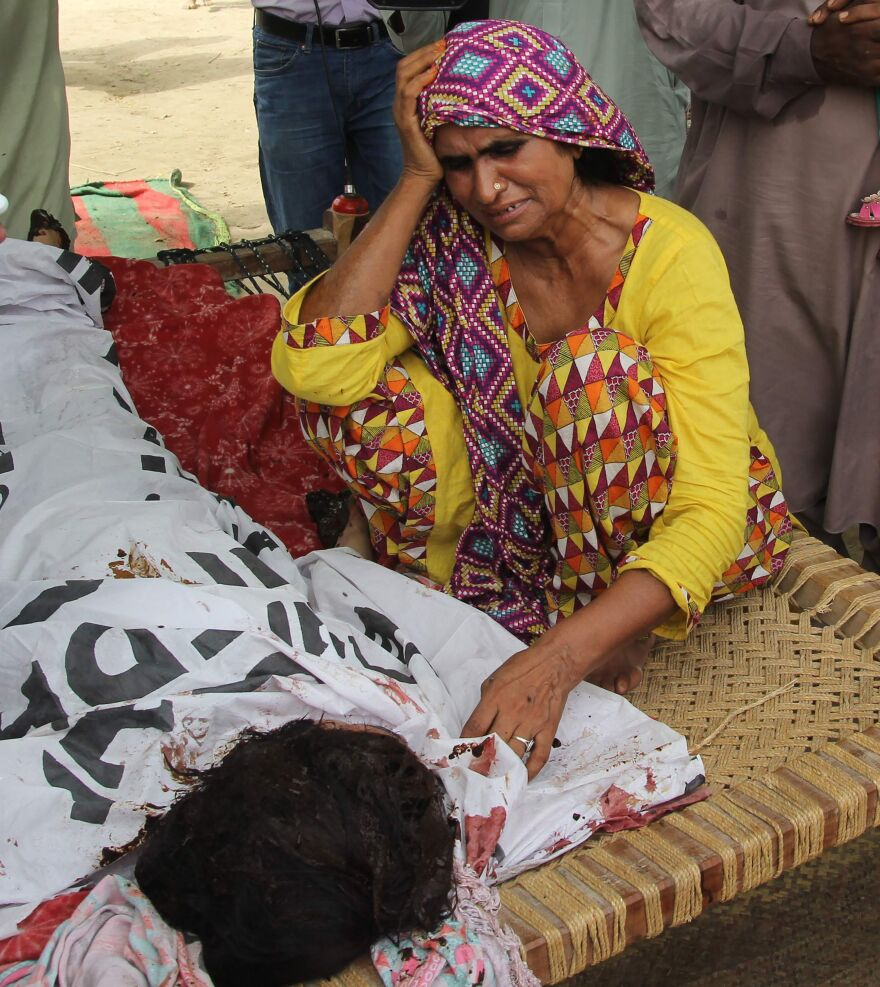 Anwar Bibi, Qandeel Baloch's mother, mourns alongside her daughter's body during her funeral in Punjab's Shah Sadar Din village on July 17.
