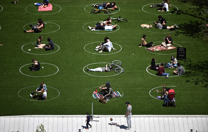 Signs and circles — directing people where to move, stand, or lie down — popped up in many public spaces including in Brooklyn's Domino Park.