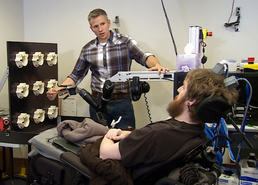 Robert Gaunt tests Nathan Copeland's ability to detect touch by tapping fingers on a robotic hand.