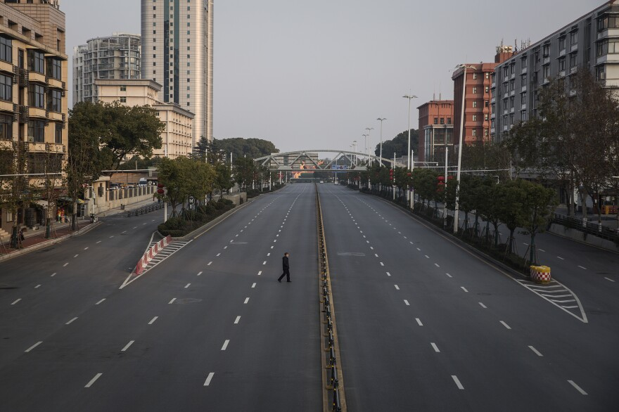 A man crosses an empty road in Wuhan, Hubei province, China, on Feb. 3, 2020.