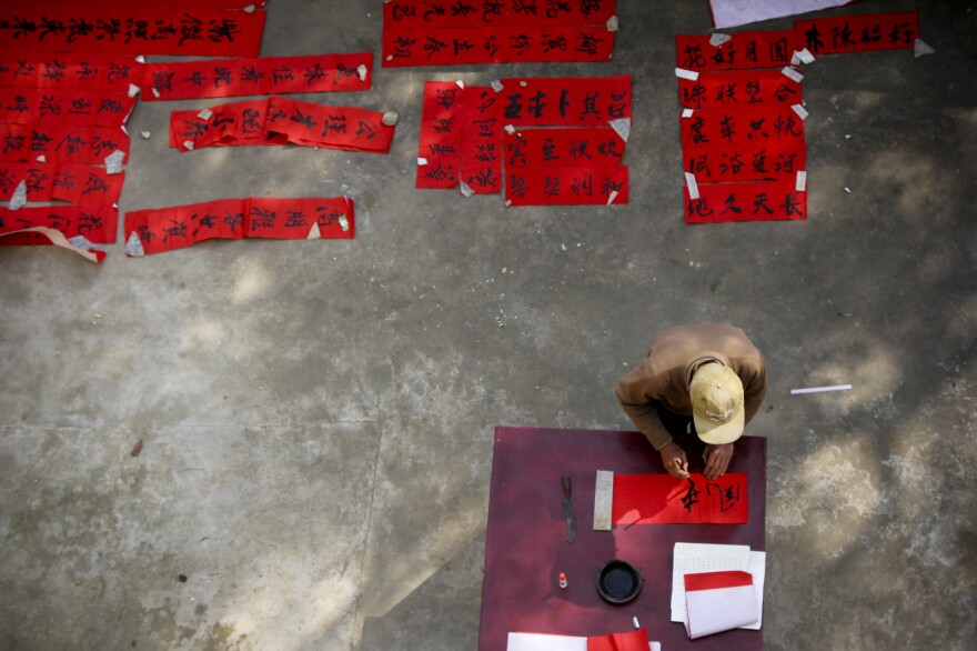 Many people now buy pre-made Chinese couplets to hang along the edges of the door frames of their homes, but Rocky wanted the real thing — so the village calligrapher used a brush and ink to craft these couplets for Rocky's big day.