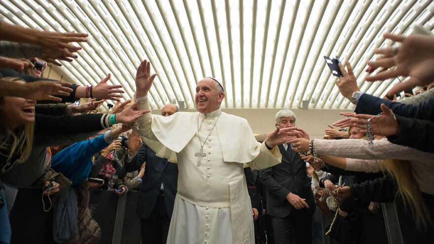 Pope Francis is cheered by the faithful as he arrives for the weekly general audience at the Vatican on Wednesday.