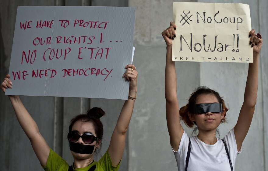 Anti-coup protesters hold placards during a gathering at the Victory Monument in Bangkok on Sunday.