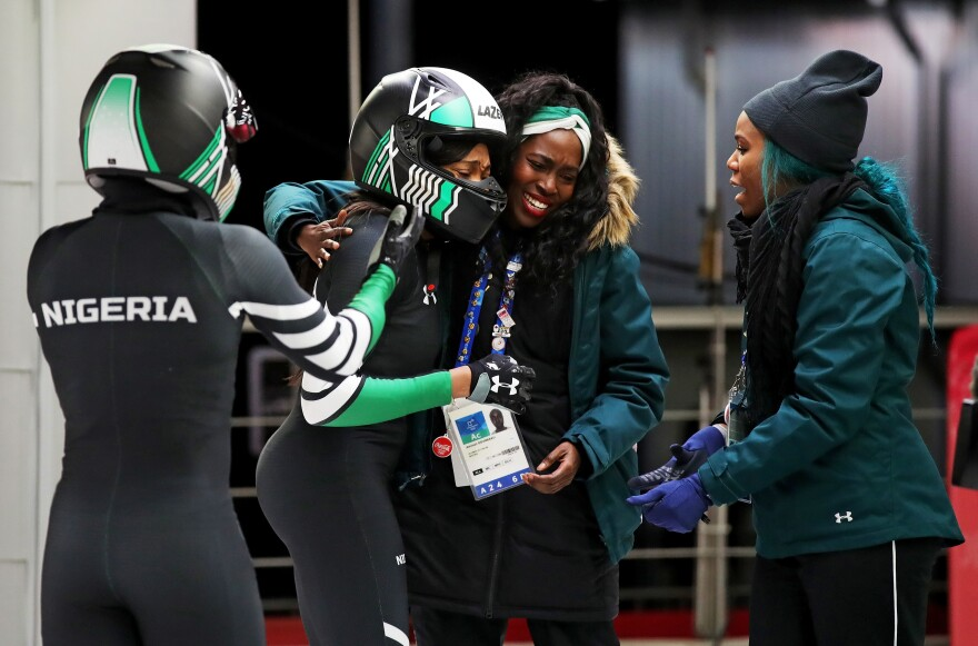 Nigerian bobsledder Akuoma Omeoga (second left) embraces teammate Aminat Odunbaku (second right) during the women's bobsled heats on Feb. 21.