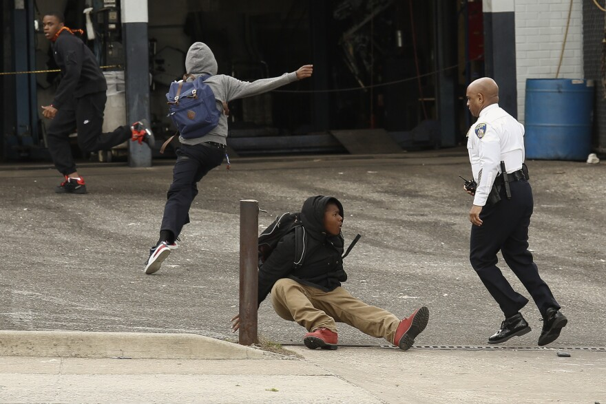 Baltimore Police Commissioner Anthony Batts chases some young men in a parking lot on Reisterstown Road near Mondawmin Mall.