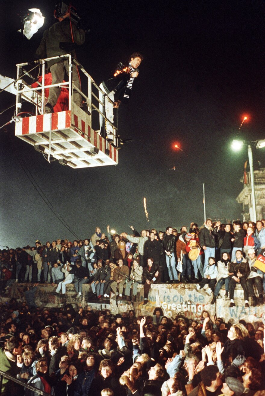 """David Hasselhoff hovers in the cage of a hoisting crane above the Berlin Wall and sings """"Looking for Freedom"""" on Dec. 31, 1989."""