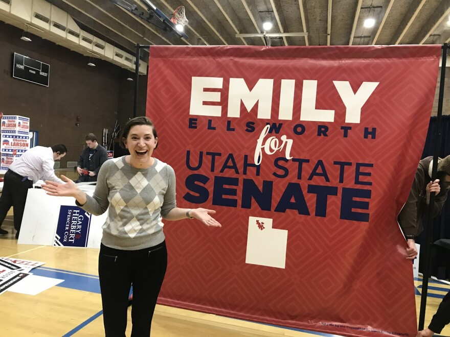 """Photo of a woman standing in from of a large red sign that reads """"Emily Ellsworth for Utah State Senate."""""""