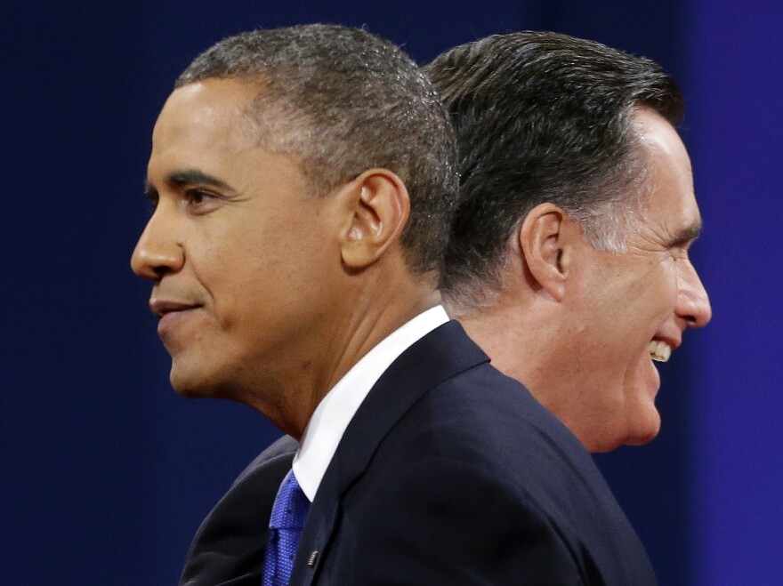 Mitt Romney and President Obama walk past each other after debating Monday in Boca Raton, Fla.