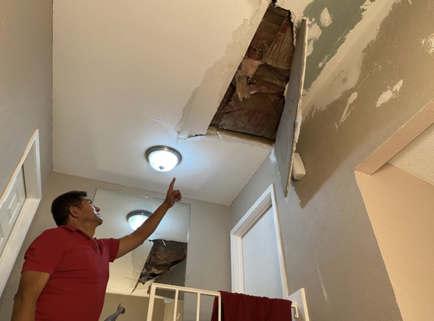 A man points to a large hole in his ceiling, with a portion of the ceiling hanging off it.