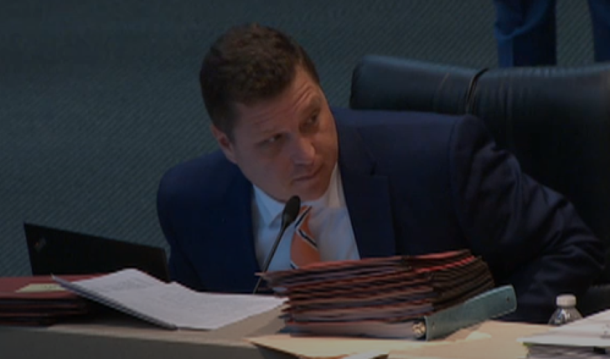 Jeff Brandes wears a blue suit with a red tie. He sits at a desk and leans over to look to his right at the person who is speaking.