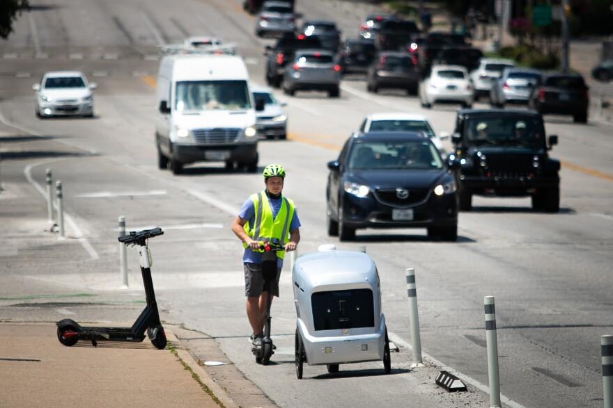 Riley Pakes, integrante de la compañía robótica Refraction AI, monitorea el desempeño de un robot de entregas a domicilio que viaja por el centro de Austin el 16 de junio.
