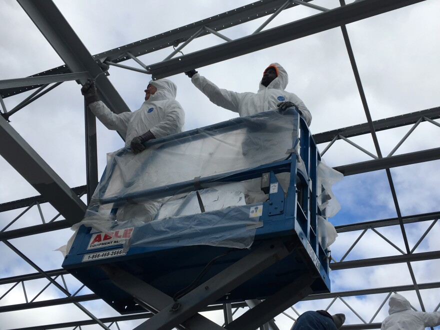Lionel Henry (right), who works for a minority-owned contracting firm, repairs the roof of an outdoor hockey rink at Philadelphia's Fishtown Recreation Center in December 2019. The project was part of a Philadelphia effort to expand participation of minority contractors in city-funded construction jobs.