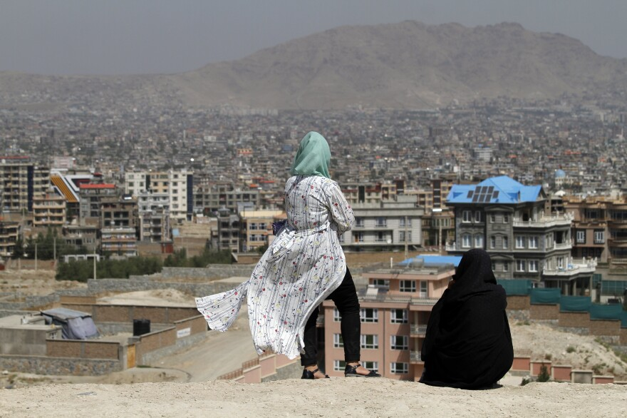 Afghan women look at the skyline of Kabul in September.