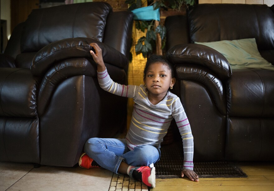 Five-year-old Amor Robinson demonstrates where she sat when she heard gunfire recently at her grandmother's home in St. Louis. The narrow gap between the couch and armchair recliner became her hideaway.