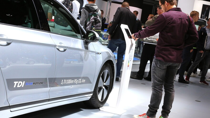 Visitors look at Volkswagen cars at the 2015 IAA Frankfurt Auto Show in Germany on Monday. Volkswagen CEO Martin Winterkorn has apologized to customers over a scandal involving emissions in its diesel cars.