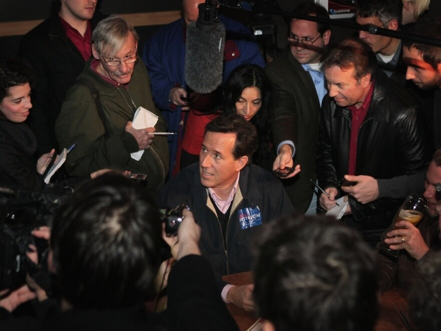 Former Pennsylvania Sen. Rick Santorum is mobbed by press while hosting a Pinstripe Bowl watch party at Buffalo Wild Wings Grill and Bar on Friday in Ames, Iowa.