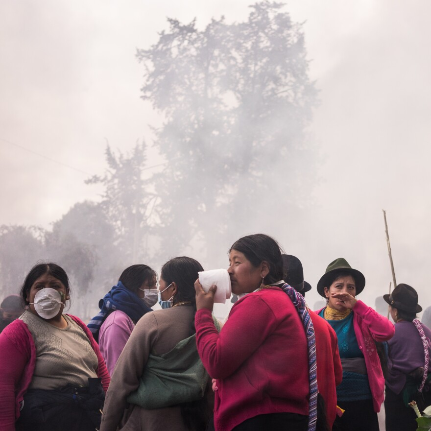 Women from the Otavalo community cover their faces in front of tear gas during the October, 2019 protests in Quito, Ecuador.