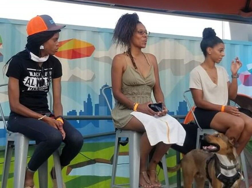 Three Black women sitting on stools on a stage with their dogs in front of a painted backdrop showing the Kansas City skyline.
