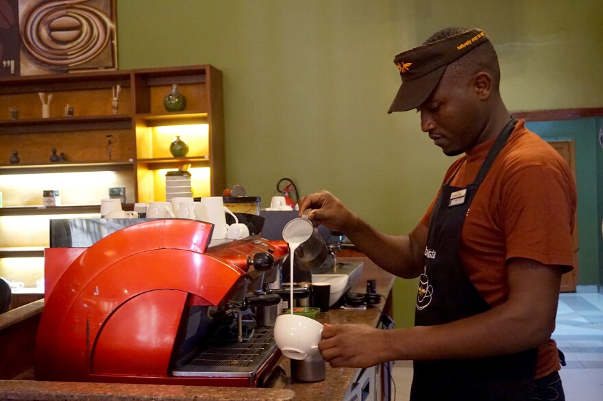 Mihigo Jones, 25, a barista, makes a latte at a coffee shop in downtown Kigali. He first started drinking coffee when he began working at the shop.