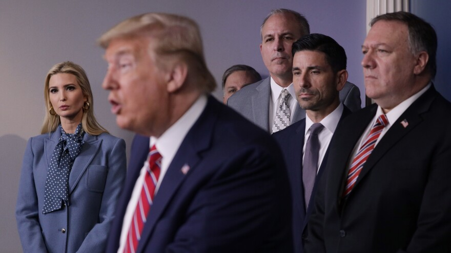 Flanked by members of the coronavirus task force, President Trump speaks during a briefing on the latest development of the coronavirus outbreak in the James Brady Briefing Room at the White House on Friday.