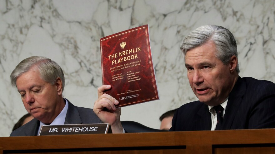 Senate Judiciary Committee member Sheldon Whitehouse, D-R.I., holds up a copy of The Kremlin Playbook while delivering remarks with Sen. Lindsey Graham, R-S.C., at the conclusion of a May 8 subcommittee hearing on Russian interference in the 2016 election.