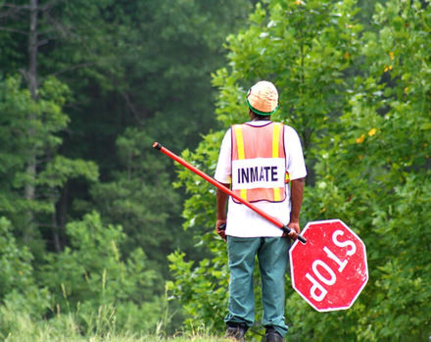 Man in orange 'inmate' vest and hard hat holds a stop sign on the side of the road.