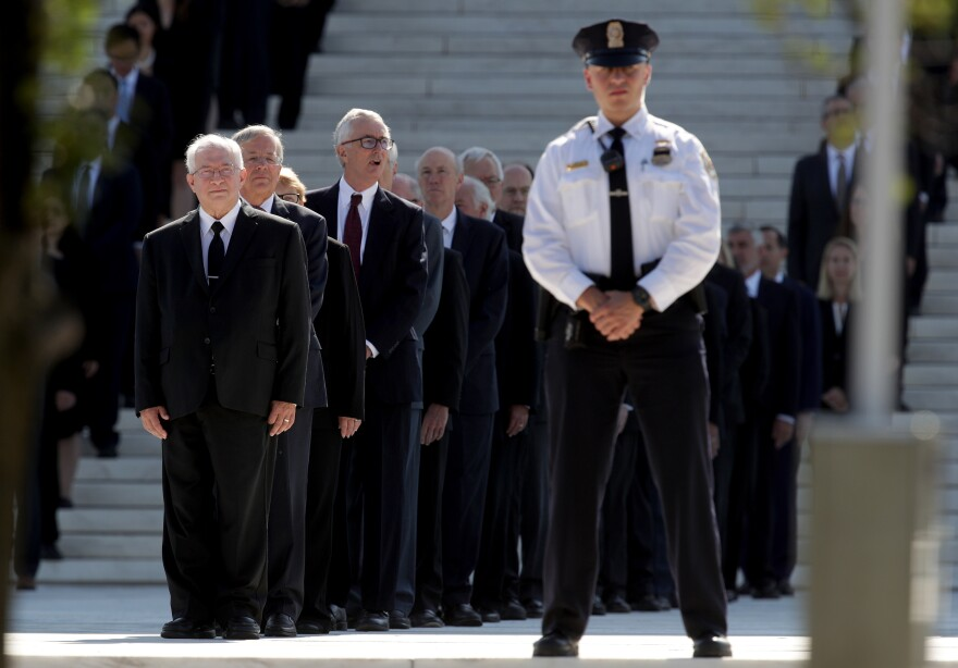 Former Supreme Court clerks watch as members of the U.S. Supreme Court police serving as pallbearers carry Stevens' casket up the steps of the Supreme Court.