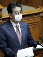 Japan's Prime Minister Shinzo Abe speaks during a plenary session at the upper house of parliament in Tokyo on Friday. Abe says he will declare a state of emergency this week in response to the coronavirus pandemic.
