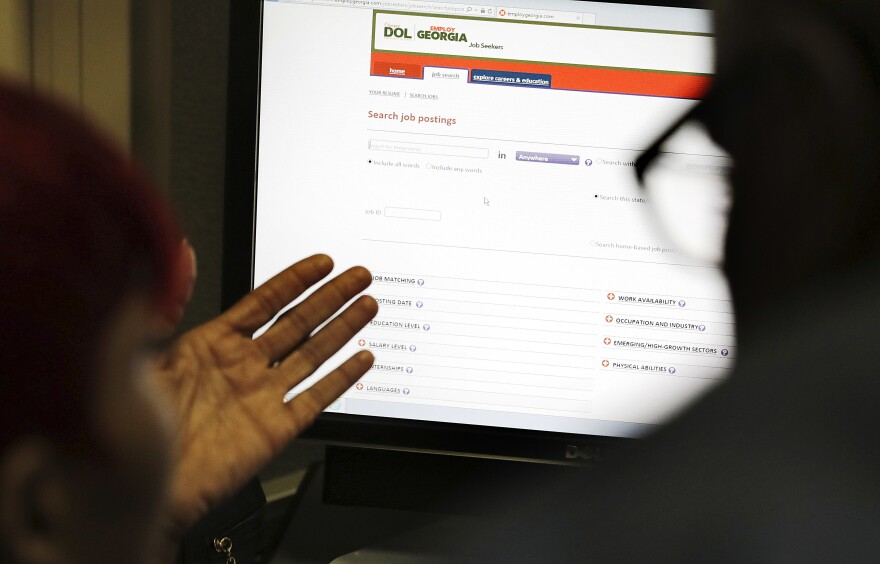 In this Thursday, March 3, 2016, file photo, Georgia Department of Labor services specialist Louis Holliday, right, helps a woman with a job search on a computer at an unemployment office in Atlanta.
