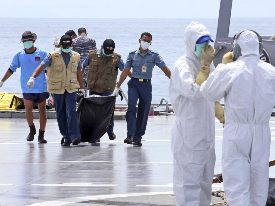 Crew members carry a bag containing the body believed to be a victim of AirAsia Flight 8501 to a waiting helicopter on the deck of Indonesian Navy ship KRI Banda Aceh, on the Java Sea, Indonesia, on Friday.