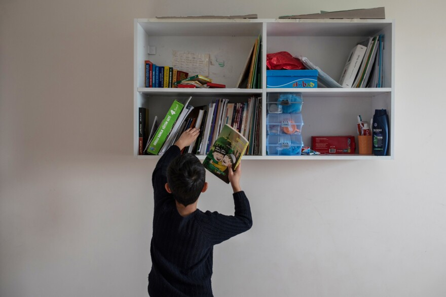 Muhammet takes a book from the bookshelf in his dormitory room. He says he wants to grow up fast so he can hack computers to learn where his parents are being detained in China.