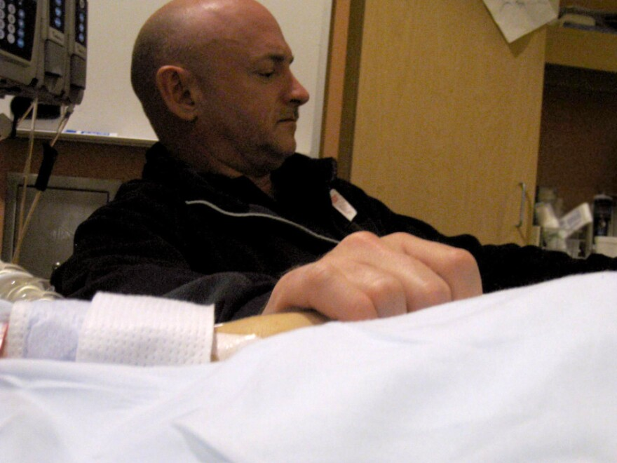 """Mark Kelly holds his wife's hand in her hospital room on Jan. 9 in Tucson, Ariz., the day after she was shot. He has had to make critical choices about her care. """"The key,"""" he tells NPR's Neal Conan, """"is knowing what requires a quick decision and what you can put off, and try to gather more information and decide later."""""""