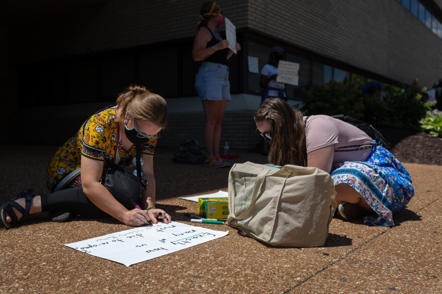 Emi Belciak, a teacher in Normandy, and Megan Rose, who teaches at North Side Community School, make posters July 13, 2020, at a protest over school re-opening plans during the pandemic.