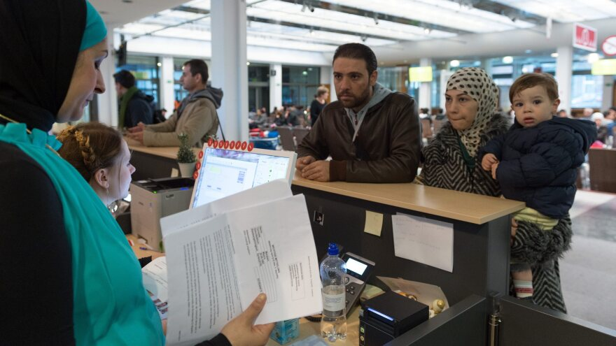A family from Syria speaks with a language professional (left) about their application for asylum.