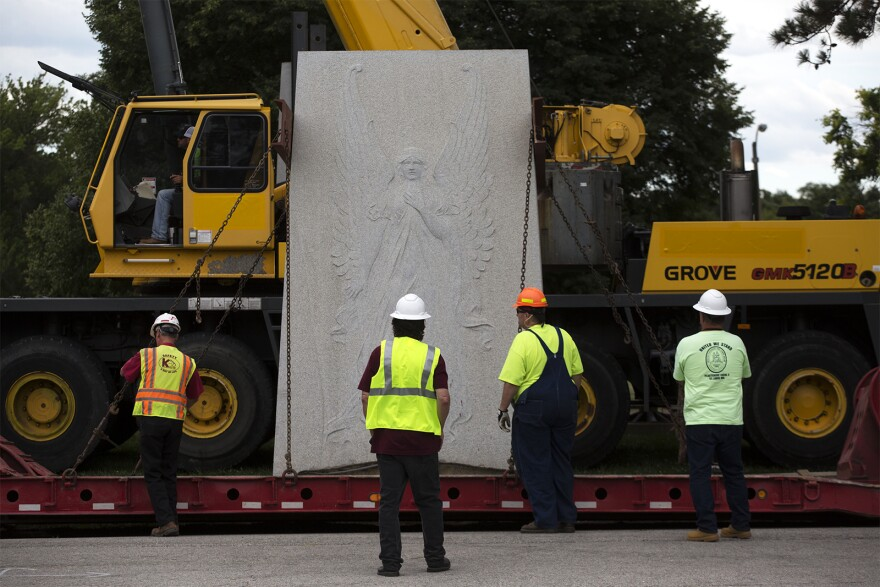 Bill Hannegan, center, thought the monument should remain and has been vocal about his opinion. He joined workers Monday as they secured part of the monument to haul it away.