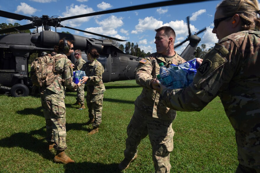 U.S. Army servicemen and women distribute water bottles and supplies.