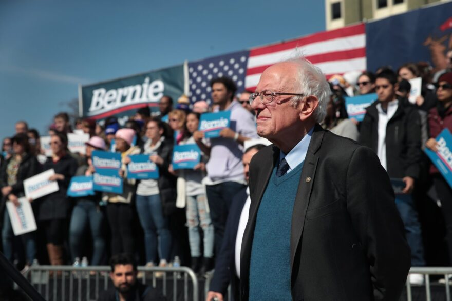 Democratic presidential candidate Sen. Bernie Sanders (I-VT) listens as Rev. Jesse Jackson addresses the crowd during Sander's campaign rally in Calder Plaza in Grand Rapids, Michigan.