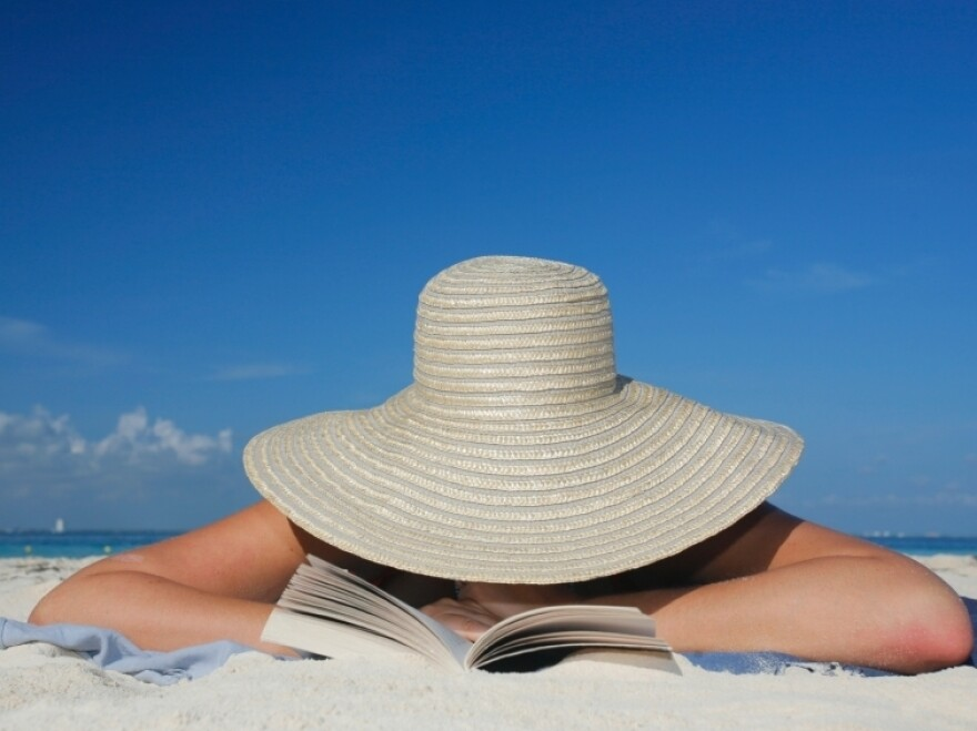 A woman reads on the beach.
