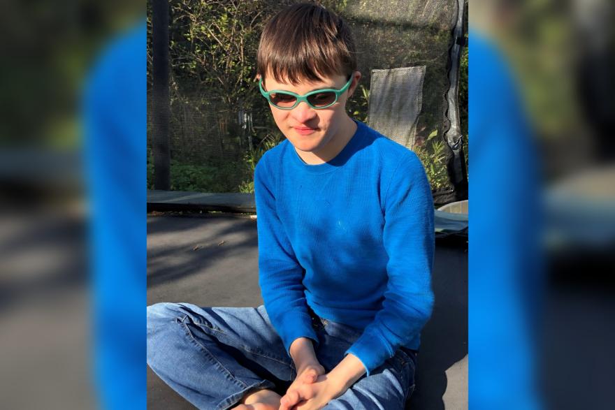 A teenage wearing glasses and a blue shirt sits cross-legged on some asphalt.